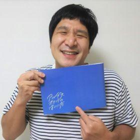 パンフレットを持つ鯉八さん